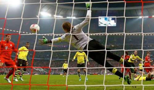 Goalkeeper Roman Weidenfeller of Borussia Dortmund dives to make save against Bayern Munich during their German first division Bundesliga soccer match in Munich